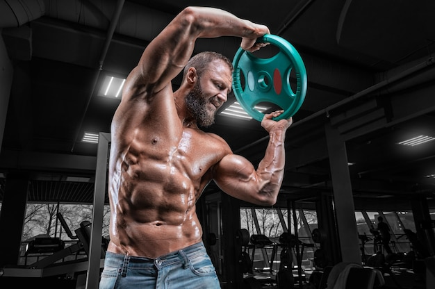 Professional athlete trains with a barbell disc in the gym. bodybuilding and fitness concept.