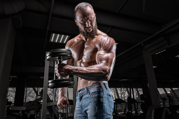 Professional athlete trains with a dumbbell in the gym. bicep pumping. bodybuilding and fitness concept.