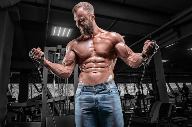Professional athlete trains with elastic bands in the gym. bodybuilding and fitness concept.