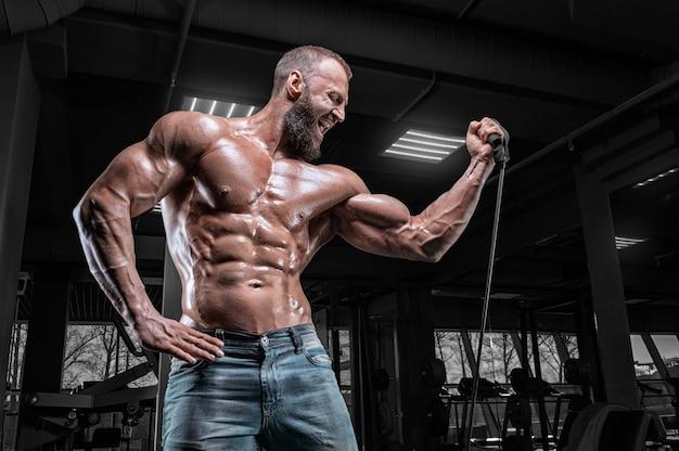 Профессиональный спортсмен тренируется на резинках в тренажерном зале. бодибилдинг и фитнес-концепция.