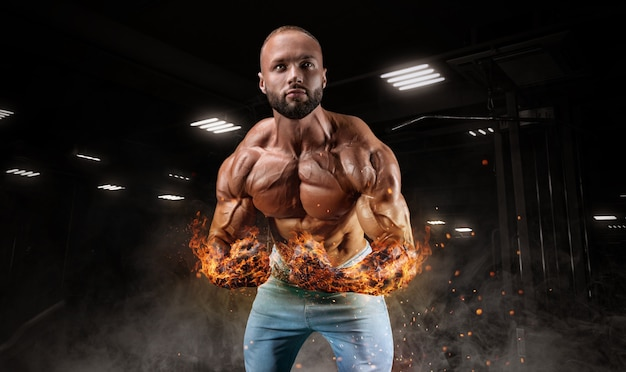 Профессиональный спортсмен с огненными руками позирует в тренажерном зале. бодибилдинг, фитнес, спортивная концепция. смешанная техника