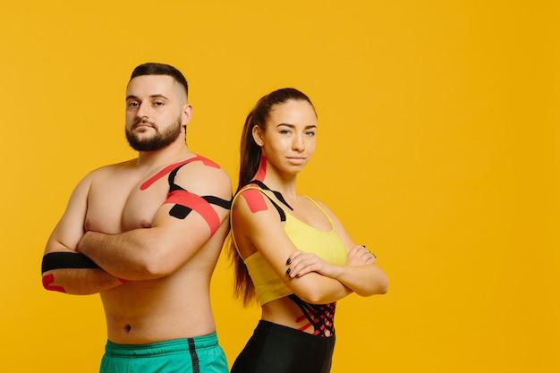 プロのスポーツ選手、男性と女性の体にキネシオロジーテープで黄色のポーズ