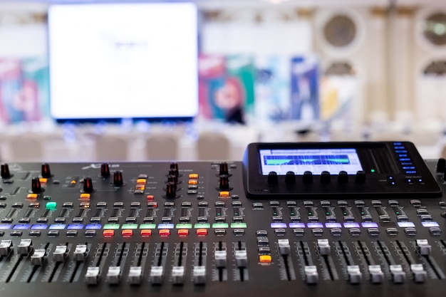 Professional audio sound mixing console faders in seminar room.
