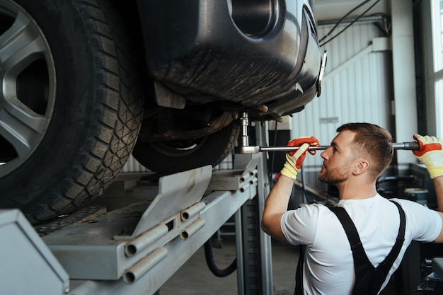 Профессиональный автомеханик, работающий на ходовой части автомобильного старания.