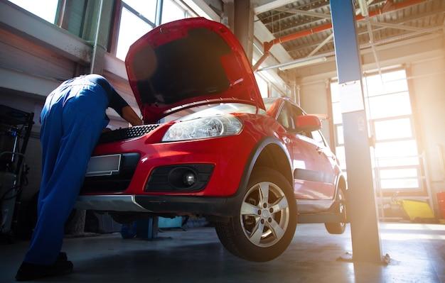 Профессиональный автомеханик ремонтирует автомобиль на сто и использует специальные инструменты.