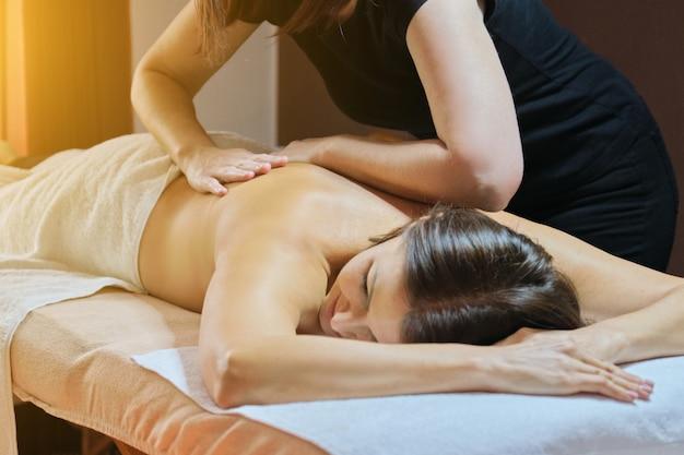 Процедура профессионального массажа спины, взрослая женщина, проходящая лечение