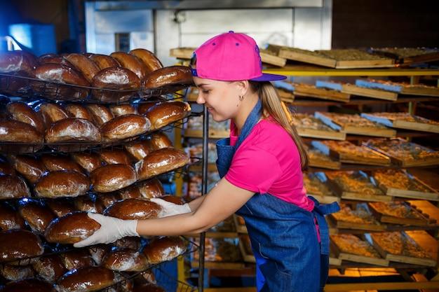 プロのパン屋-ジーンズのエプロンを着た若いきれいな女性が、パン屋やパン屋を背景に焼きたてのパンを持っています。ベーカリー製品。パンの生産