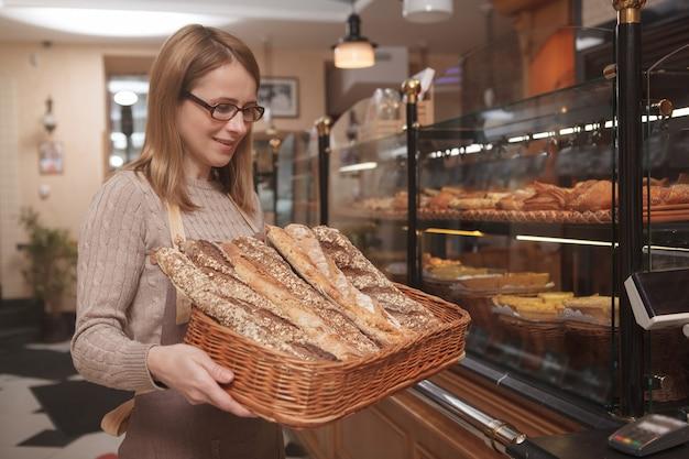 빵 바구니를 들고 그녀의 베이커리 샵에서 일하는 전문 베이커