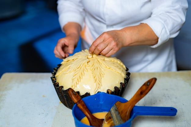 甘いパンを準備するプロのパン屋。生産ラインでペストリーを飾る。