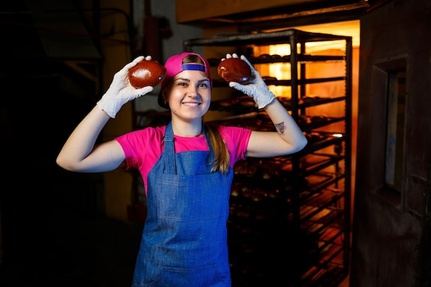 A professional baker woman holds fresh buns in her hands and hears their smell in the bakery. she is wearing a denim frock and a cap. production of bakery products. rack with hot crispy pastries.