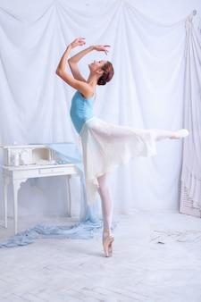 흰색 탈의실에서 포즈를 취하는 전문 발레리나 댄서