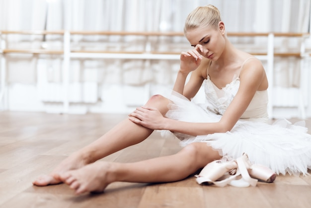 Professional ballerina is sitting on floor in dance class.