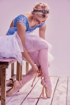 Профессиональная балерина надевает балетные туфли.