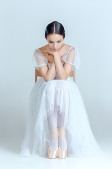 Professional ballerina sitting with her ballet shoes on the gray wall