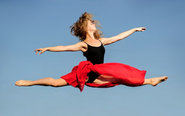 Professional ballet dancer jumping with red fabric on sunset sun.
