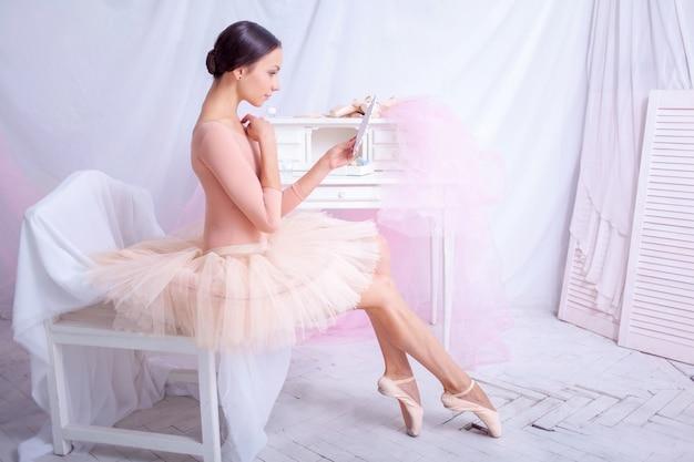Professional ballet dancer looking in mirror on pink