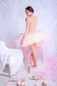 Профессиональная балерина позирует на розовом