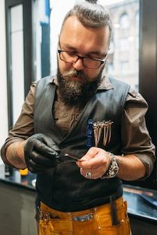 Профессиональный парикмахер проверяет ножницы перед работой