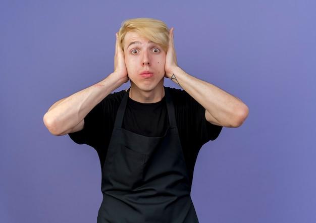 Uomo di barbiere professionista in grembiule che copre le orecchie con le mani sorprese e confuse