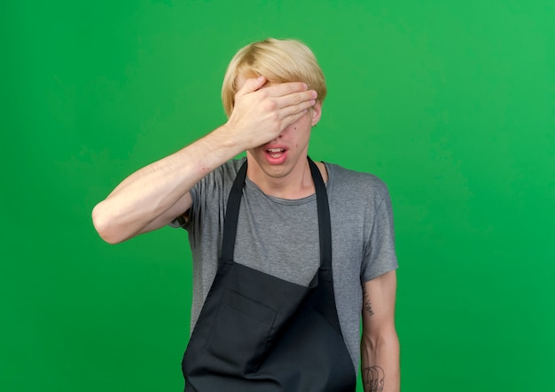 Professional barber man in apron covering eyes with hand