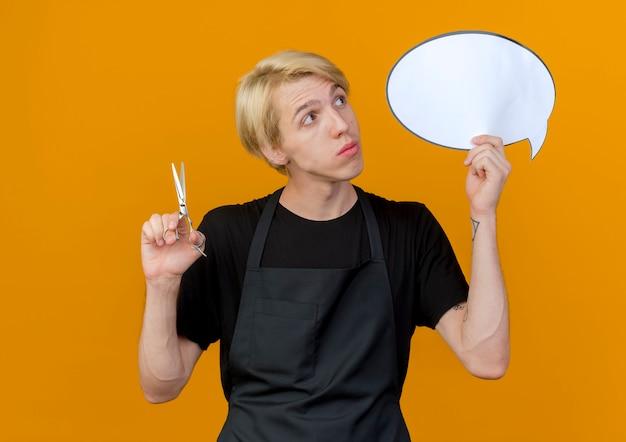 Uomo di barbiere professionista in grembiule che tiene segno in bianco della bolla di discorso e forbici che osserva da parte in piedi perplesso sopra la parete arancione