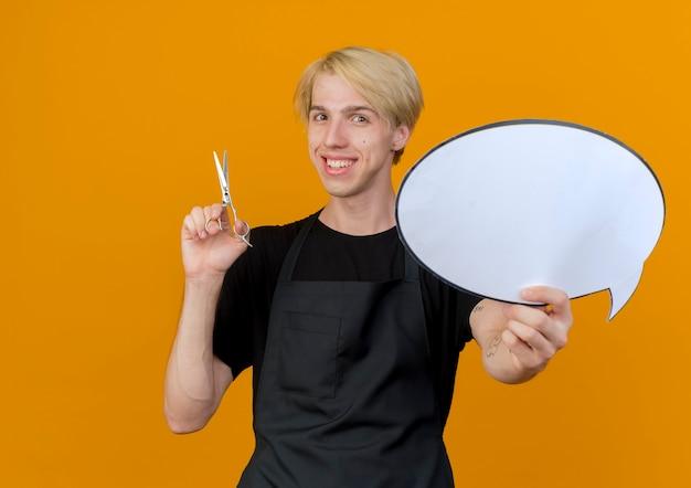 Uomo del barbiere professionista in grembiule che tiene il segno in bianco della bolla di discorso e le forbici che esaminano la parte anteriore che sorride con la faccia felice che sta sopra la parete arancione