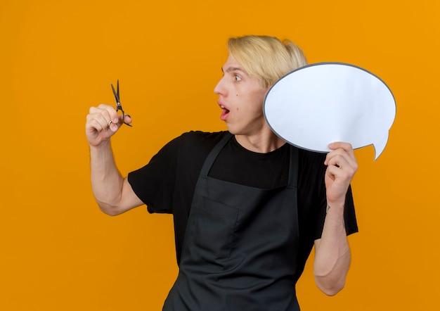 Uomo di barbiere professionista in grembiule che tiene segno di bolla di discorso in bianco e forbici guardando le forbici stupito in piedi sopra la parete arancione