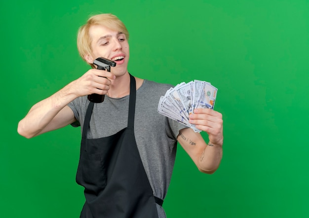 Professional barber man in apron holding cash and spray happy and positive smiling