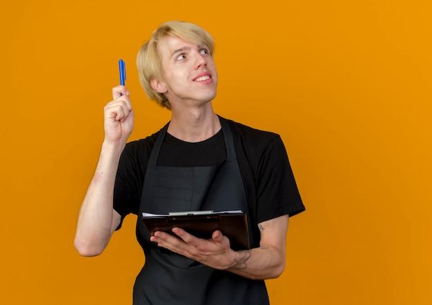 Uomo di barbiere professionista in grembiule che tiene appunti e penna che guarda da parte felice e sorpreso avendo nuova idea in piedi sopra la parete arancione