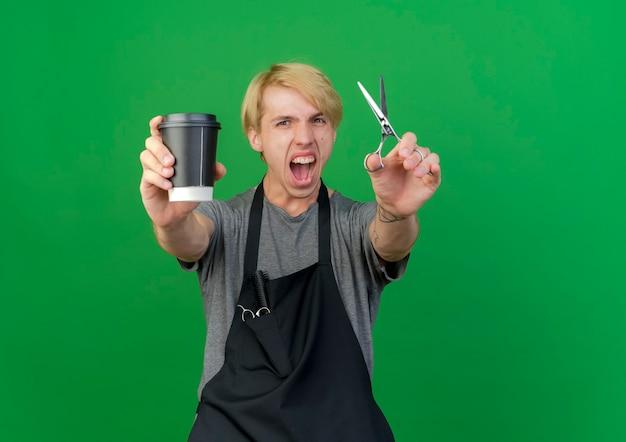 Uomo del barbiere professionista in grembiule che tiene tazza di caffè e forbici che gridano eccitato andando selvaggio