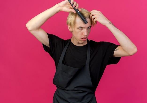 Barbiere professionista in grembiule che tiene una spazzola per capelli che si pettina i capelli con una faccia seria in piedi