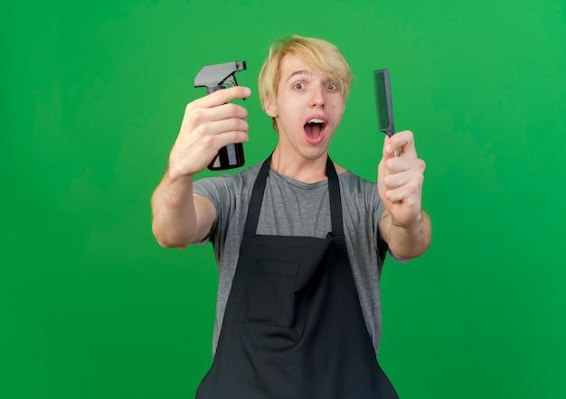 Uomo di barbiere professionista in grembiule che tiene pettine per capelli e spray sorridente felice e positivo