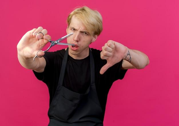 Barbiere professionista uomo in grembiule tenendo le forbici che mostra i pollici verso il basso essendo scontento in piedi sopra il muro rosa