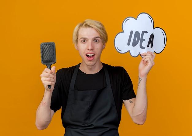 Uomo del barbiere professionista in grembiule che tiene il segno della bolla di discorso con idea di parola e spazzola per capelli guardando davanti in piedi sorpreso e felice sopra la parete arancione