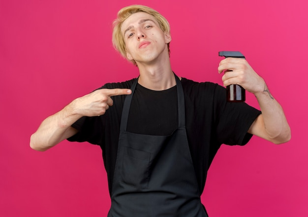 Professional barber man in apron holding spray pointing with index finger at it with serious face