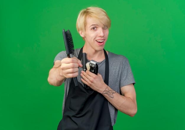 Uomo di barbiere professionista in grembiule che tiene trimmer e spazzole per capelli offrendo pennello alla telecamera sorridendo