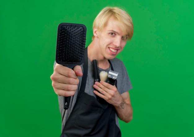 Barbiere professionista uomo in grembiule che tiene trimmer e spazzole per capelli offrendo spazzola per capelli davanti sorridente in piedi sopra la parete verde