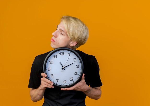 Uomo di barbiere professionista in grembiule che tiene l'orologio da parete che osserva da parte con la faccia seria che sta sopra la parete arancione