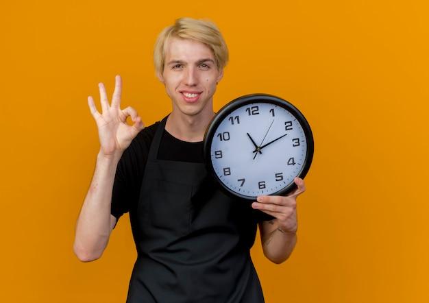 Barbiere professionista uomo in grembiule tenendo l'orologio da parete guardando la parte anteriore che mostra segno giusto in piedi sopra la parete arancione