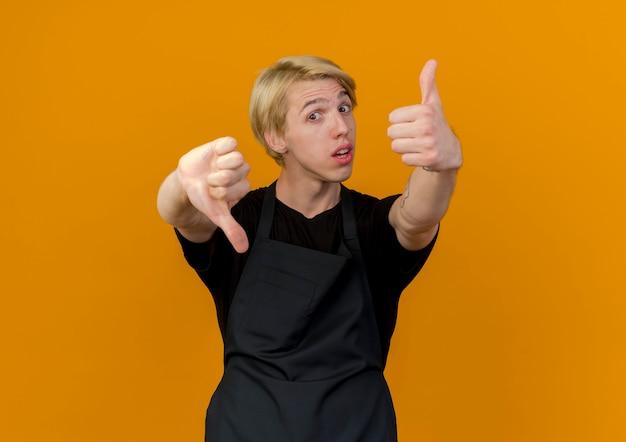 Barbiere professionista uomo in grembiule guardando davanti confuso mostrando i pollici su e giù in piedi sopra la parete arancione