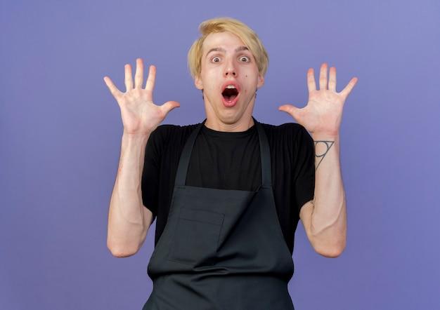 Uomo del barbiere professionista in grembiule che alza le palme in segno di resa essendo spaventato