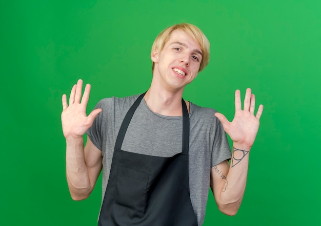 Uomo di barbiere professionista in grembiule che alza le palme in segno di resa sorridente