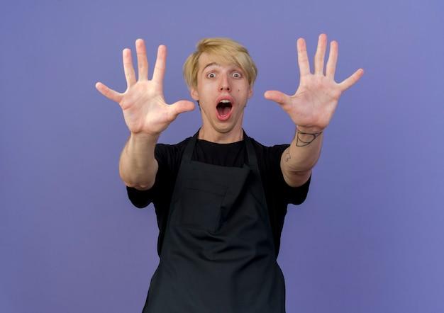 Uomo di barbiere professionista in grembiule che mostra e rivolto verso l'alto con le dita numero dieci essere sorpreso