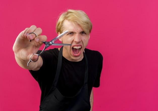 Barbiere professionista in grembiule che mostra le forbici che gridano con un'espressione aggressiva in piedi