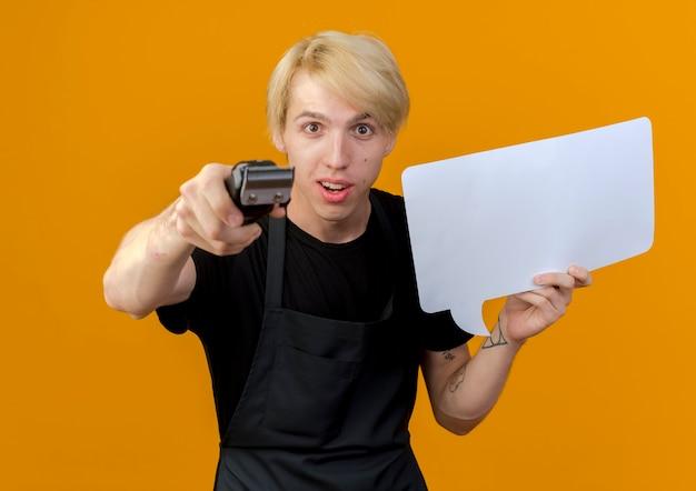 오렌지 벽 위에 서 웃는 앞에 트리머를 가리키는 빈 연설 거품 기호를 들고 앞치마에 전문 이발사 남자