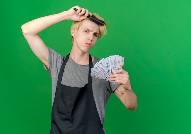 Профессиональный парикмахер в фартуке держит деньги и расческу для волос, расчесывая волосы с серьезным лицом