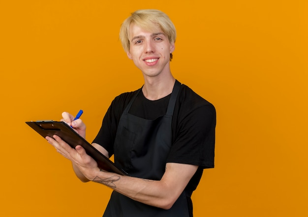 オレンジ色の壁の上に立っている顔に笑顔でクリップボードとペンを保持しているエプロンのプロの理髪店の男