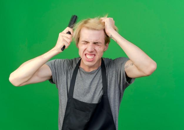 Профессиональный парикмахер в фартуке держит щетку для волос и расчесывает волосы с раздраженным выражением лица