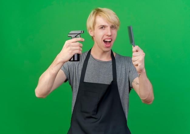 Профессиональный парикмахер в фартуке, держащий расческу и спрей для волос, выглядит счастливым и позитивным, улыбаясь, стоя на зеленом фоне
