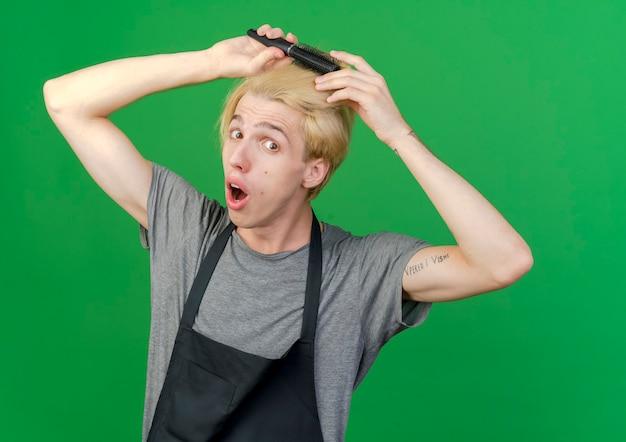 驚いたように見える彼の髪をとかす髪の櫛を保持しているエプロンのプロの理髪店の男